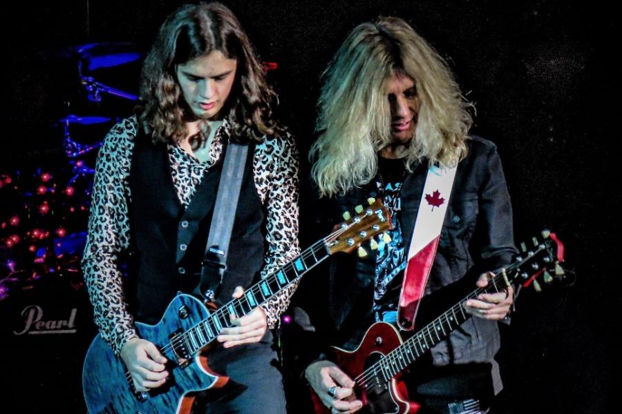 Nicholas Paré and father, Jak Paré play guitar during the concert.