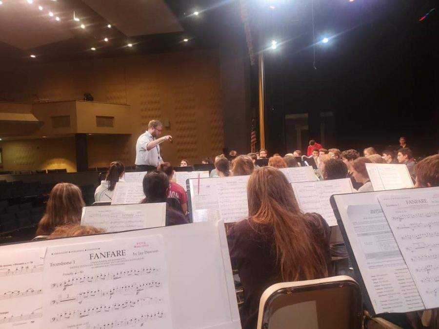 The All-County Band is practicing their piece, Fanfare.