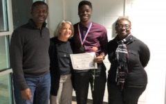 Kojo Benefo poses with his parents and Principal Nancy Doll.
