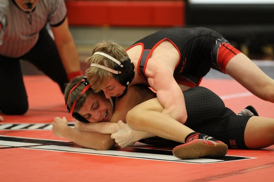 Sean Mullineaux wrestles his opponent to the ground in an intense match.