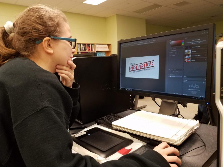Rachel Stonestreet looks over Newsies logos to use in her poster.