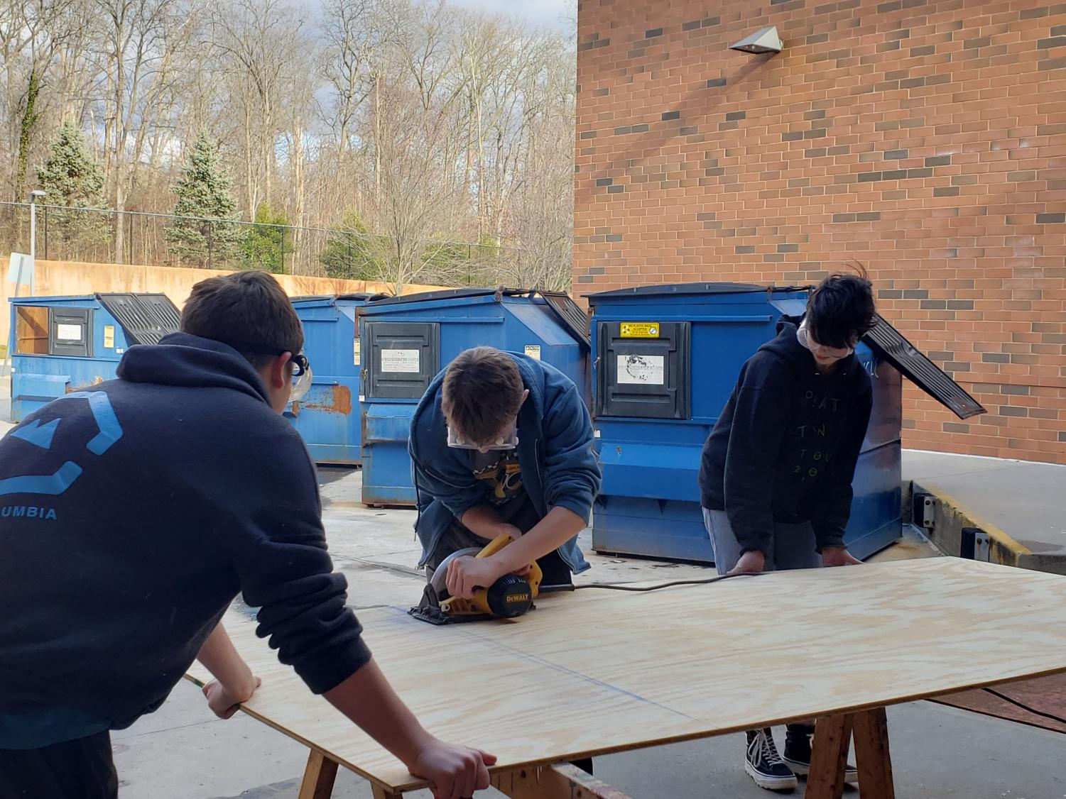 Students work together to cut a piece of wood that will be used to make a table.