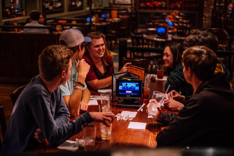 A group of students socialize at a table during UNOs Night