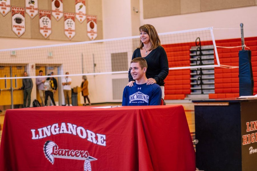 Carter Holsinger stands with his mother Michele after signing his National Letter of Intent.