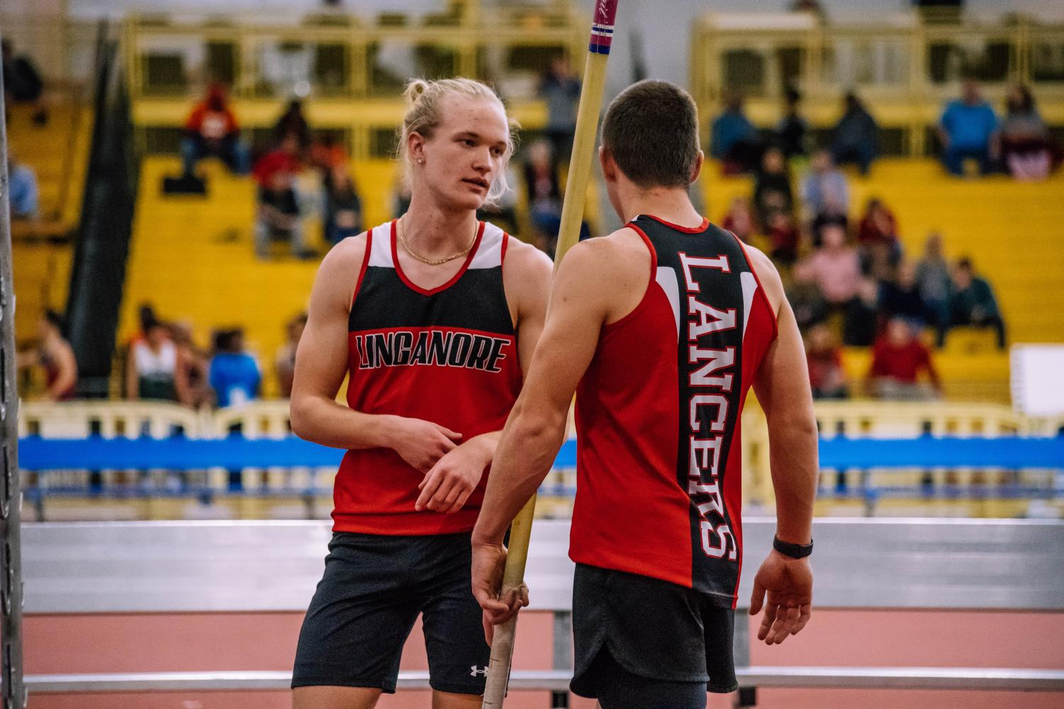 Senior pole vaulter Carter Holsinger gives sophomore pole vaulter Quinn Ruch advice before he attempts to qualify for states