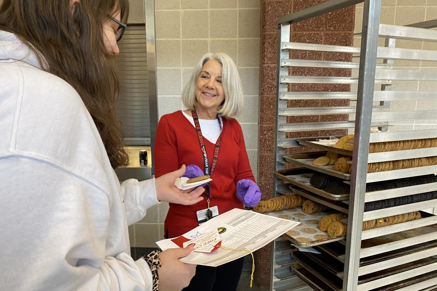Mrs. Nancy Doll hands Hannah Bowie a cookie for her success.