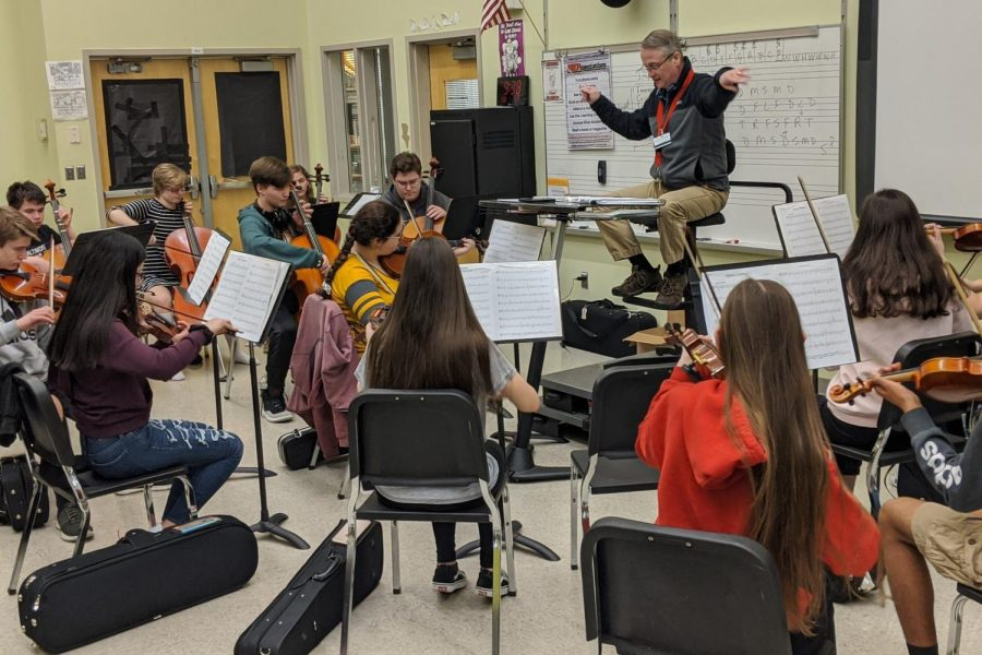 Mr. Dye conducts the orchestra through their warm-up piece, Fiddle O