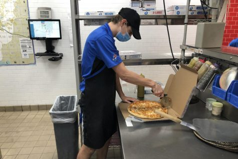 Braden Weinel cuts a pizza at work while wearing a face mask during the Covid-19 outbreak.