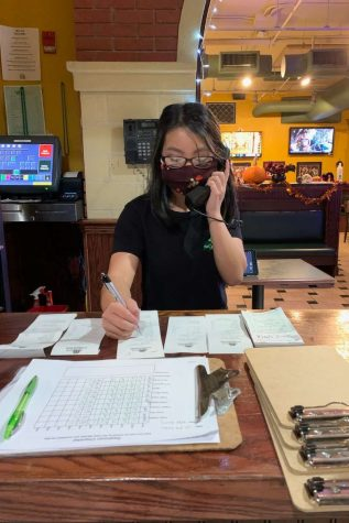 Valerie updating orders while answering the phone.