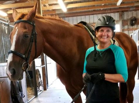 Gayle Blair with her horse in a barn on a beautiful day.
