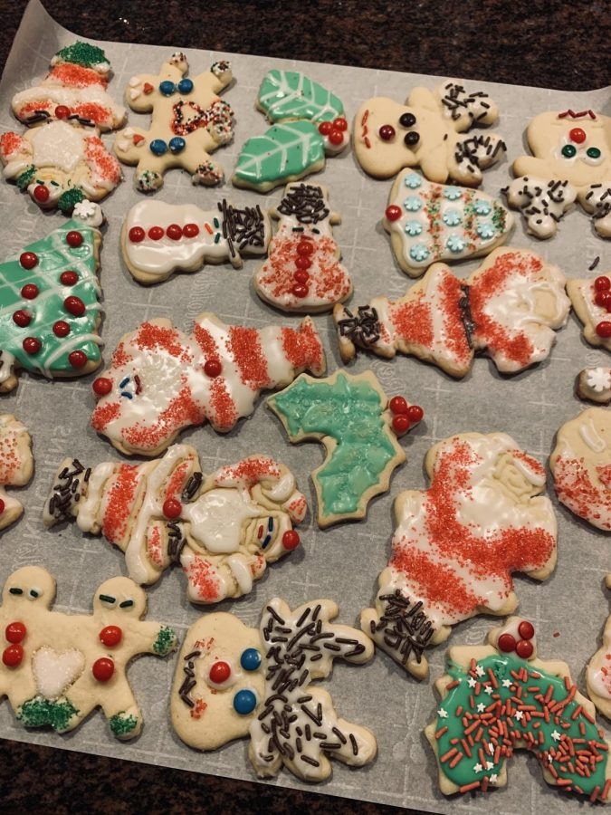 Christmas sugar cookies; santas, snowmans, christmas trees, mistletoes, silver bells, reindeers, and gingerbread men holding hands.