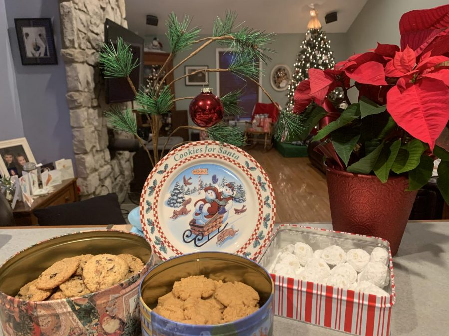 "Holiday cookies in Christmas tins surrounded by ""Cookies for Santa,"" The Peanuts Christmas tree, and a Poinsettia"