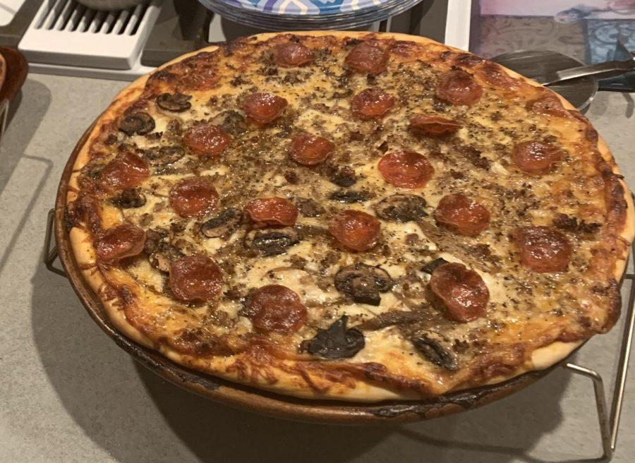 The perfect homemade pizza out of the oven with pepperoni, bacon, sausage, and mushrooms