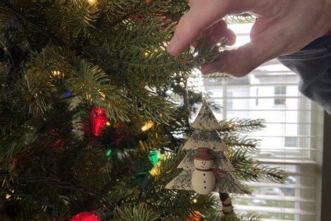Ken Spore hangs ornaments on family Christmas tree.