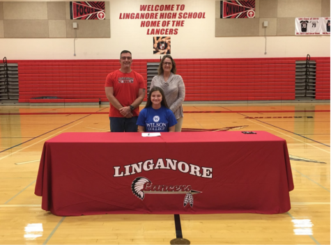 Rebecca Marakovitz smiles for a picture with her parents after signing.