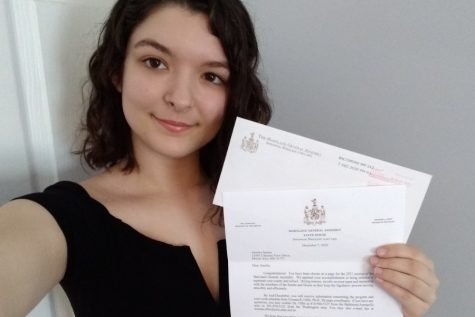 Amelia Jansen hold up her letter saying that she got into the Maryland General Assembly Student Page Program.