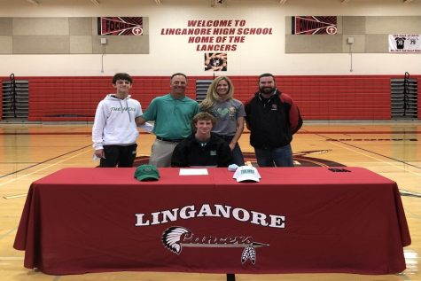Cam Rokisky smiles at the signing table for a picture with his family and high school head coach David Keiling.