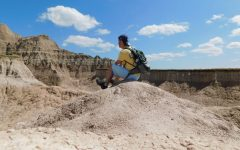 Jake Snow sitting on top of a rock in the Badlands of South Dakota before nearly falling down 500 feet