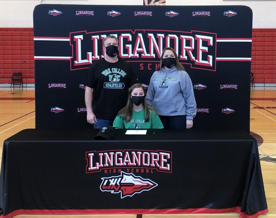 Bailey Bennett poses with her parents after signing her National Letter of Intent.