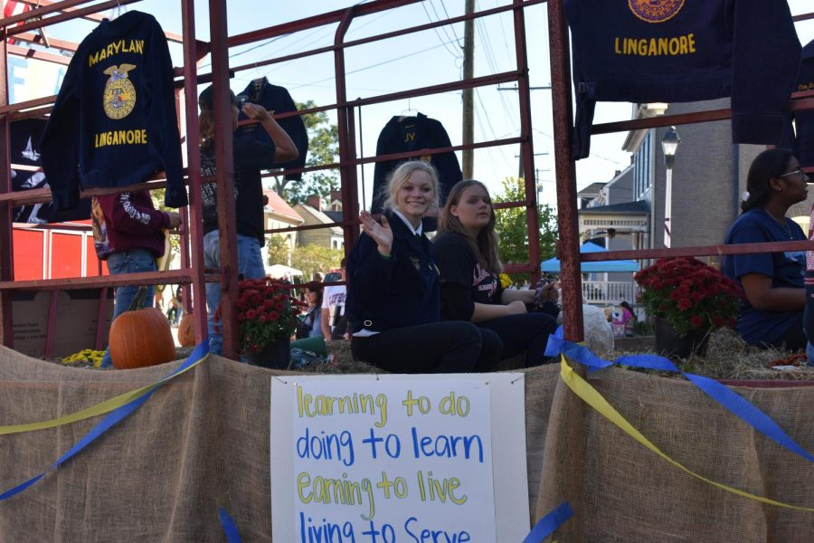 The National FFA Organization, a popular student organization at Linganore drove thought the parade attached to a tractor. Senior Shea Cencula, waves to the community as she rides along on  the float. Out of all the groups who entered floats in the parade- they all look great! The judges results placed FFA in 3rd.