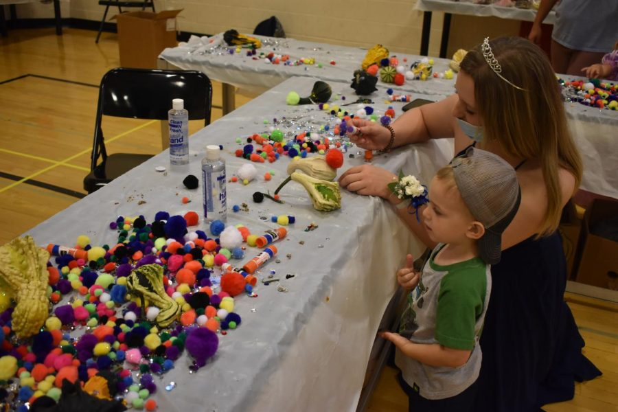 Future Linganore Lancer creates a crown for the Prince and Princess party at the arts and crafts table.