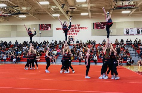 Varsity cheer team hits their stunts on the floor during Invitational.
