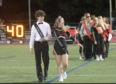 Junior Princess Molly Granger and Prince Brady Vlha accept cheers at the homecoming game.